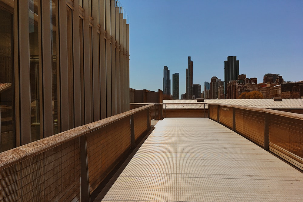 brown wooden fence near high rise buildings during daytime