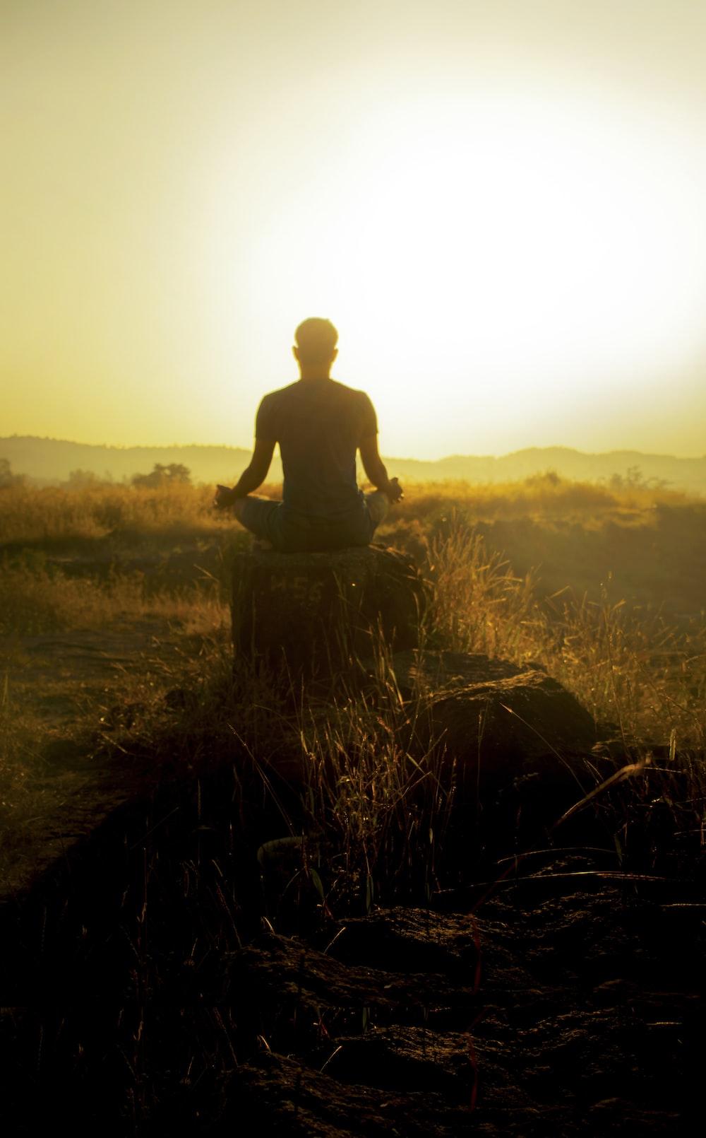 man in black shirt sitting on brown grass during daytime