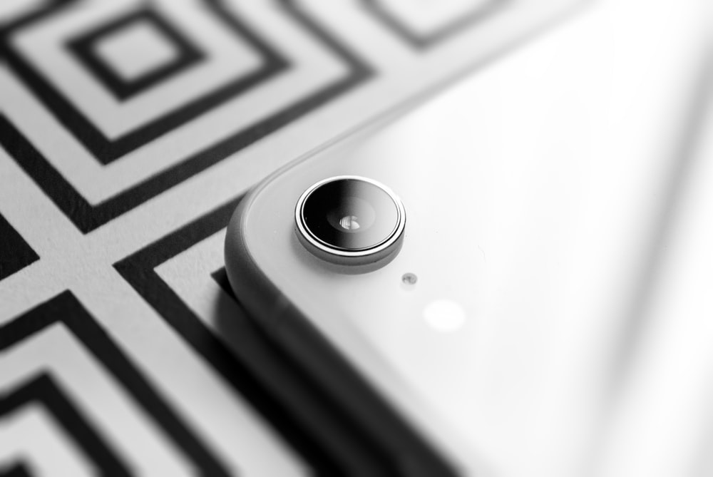 round black button on white and black textile