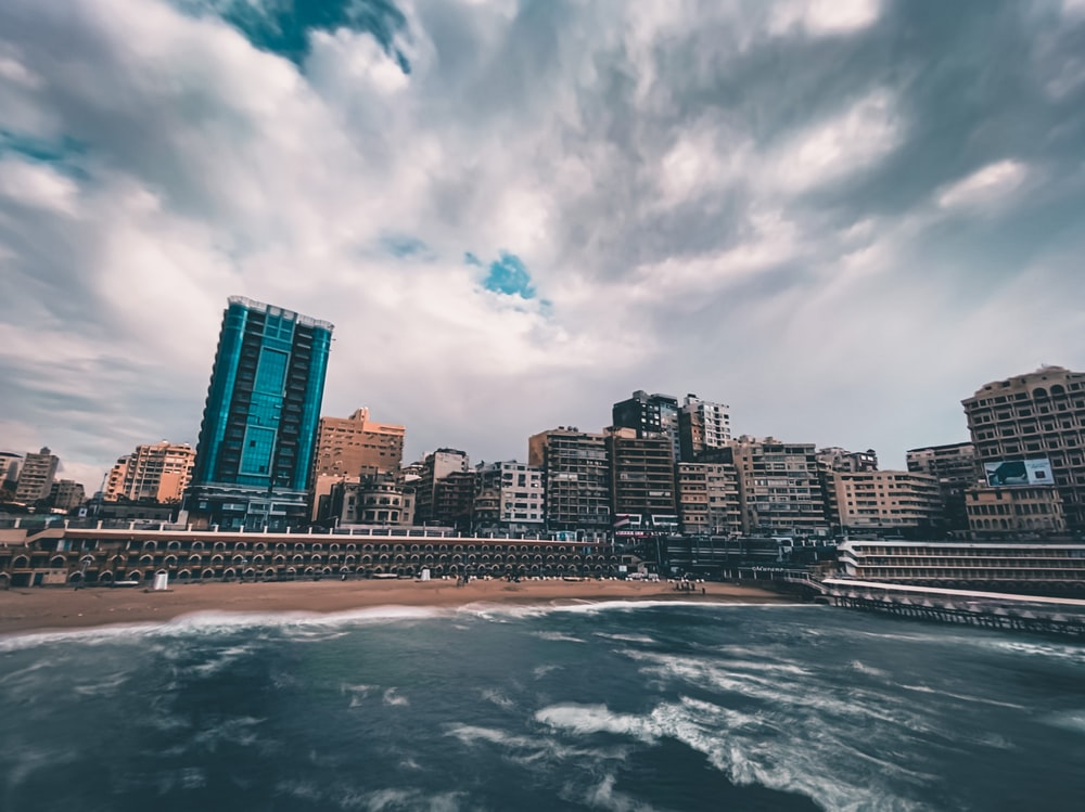 city skyline near body of water under cloudy sky during daytime