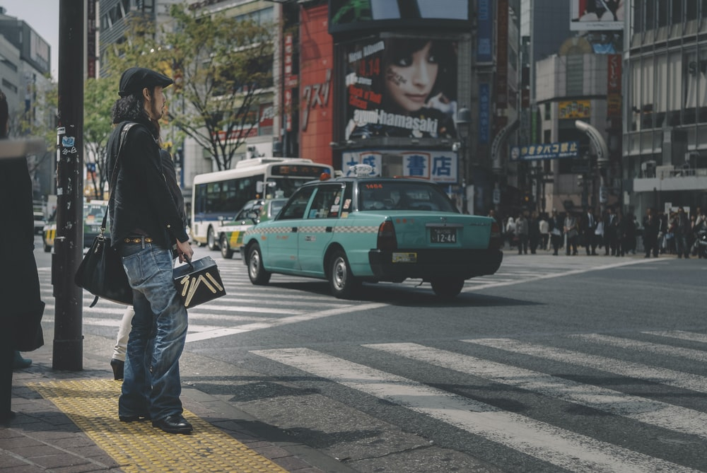 man in black jacket and blue denim jeans standing beside green car on road during daytime