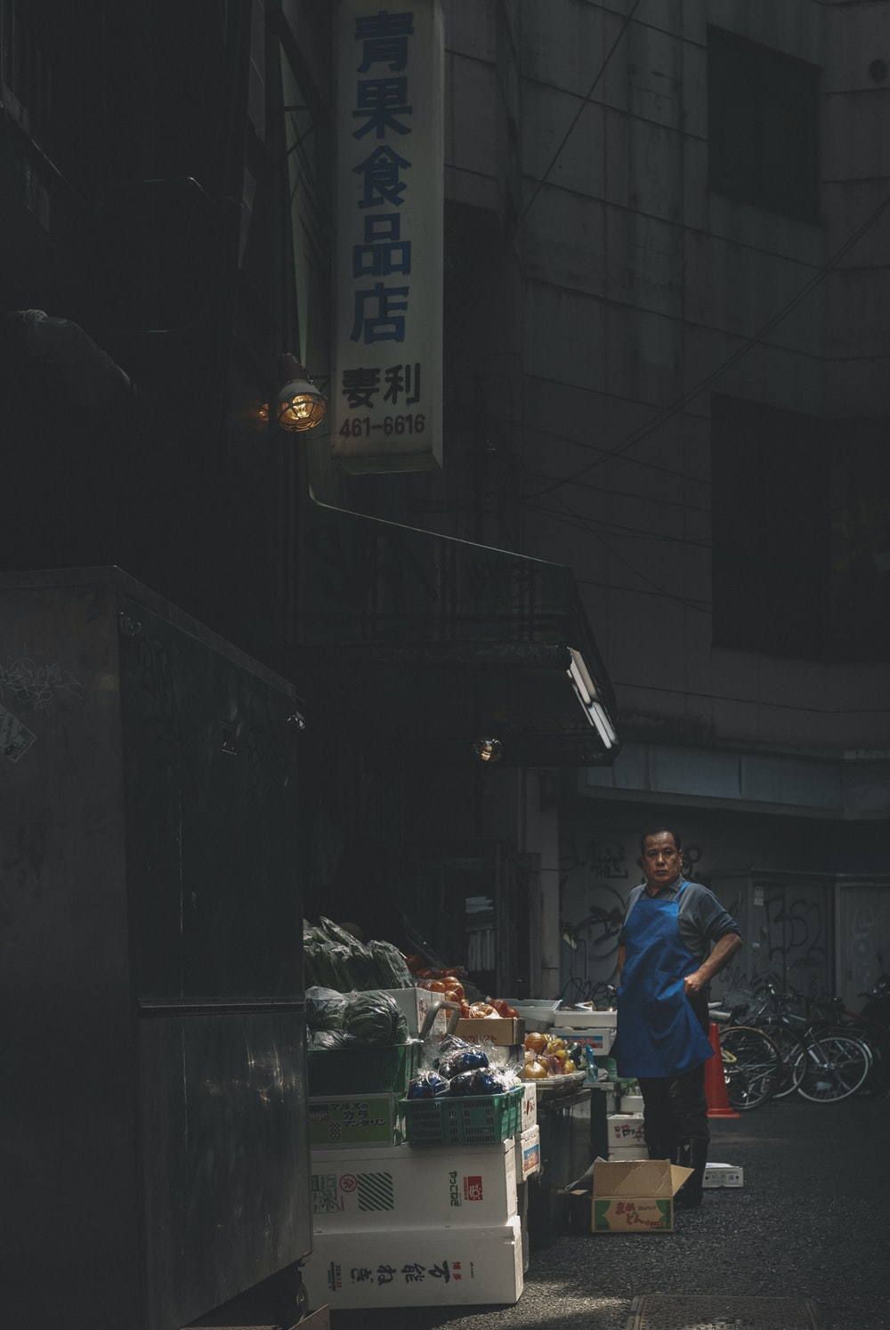 man in red t-shirt and blue denim jeans standing near food stall during nighttime