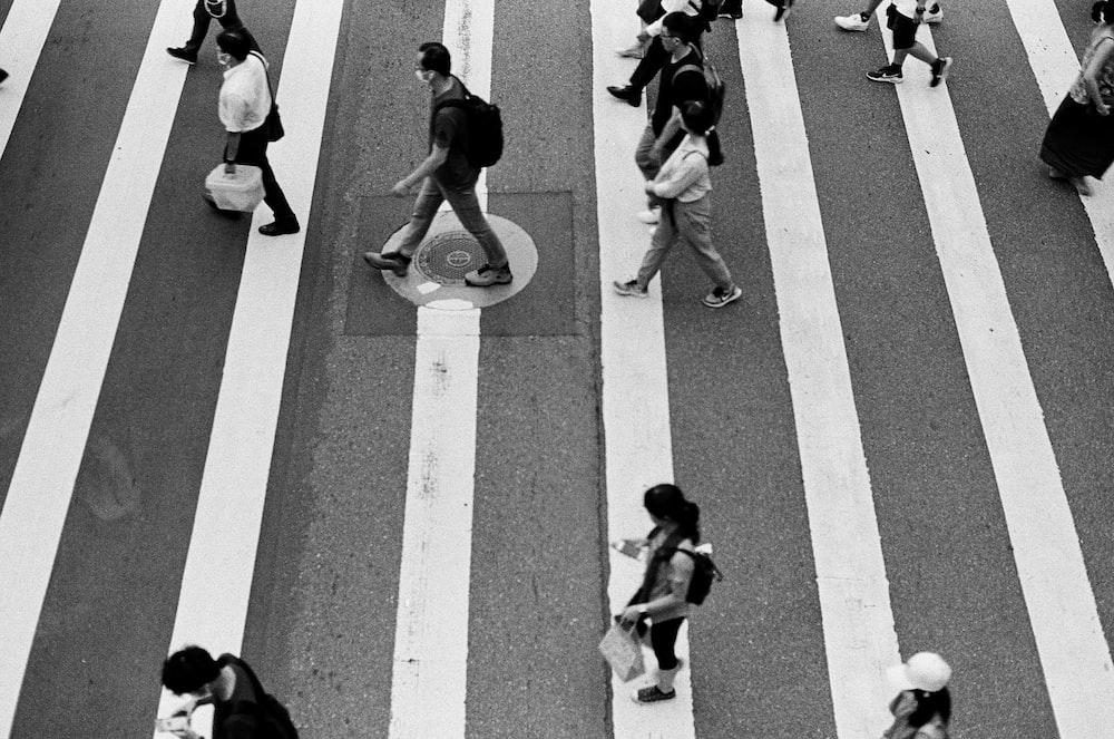 people walking on pedestrian lane in grayscale photography