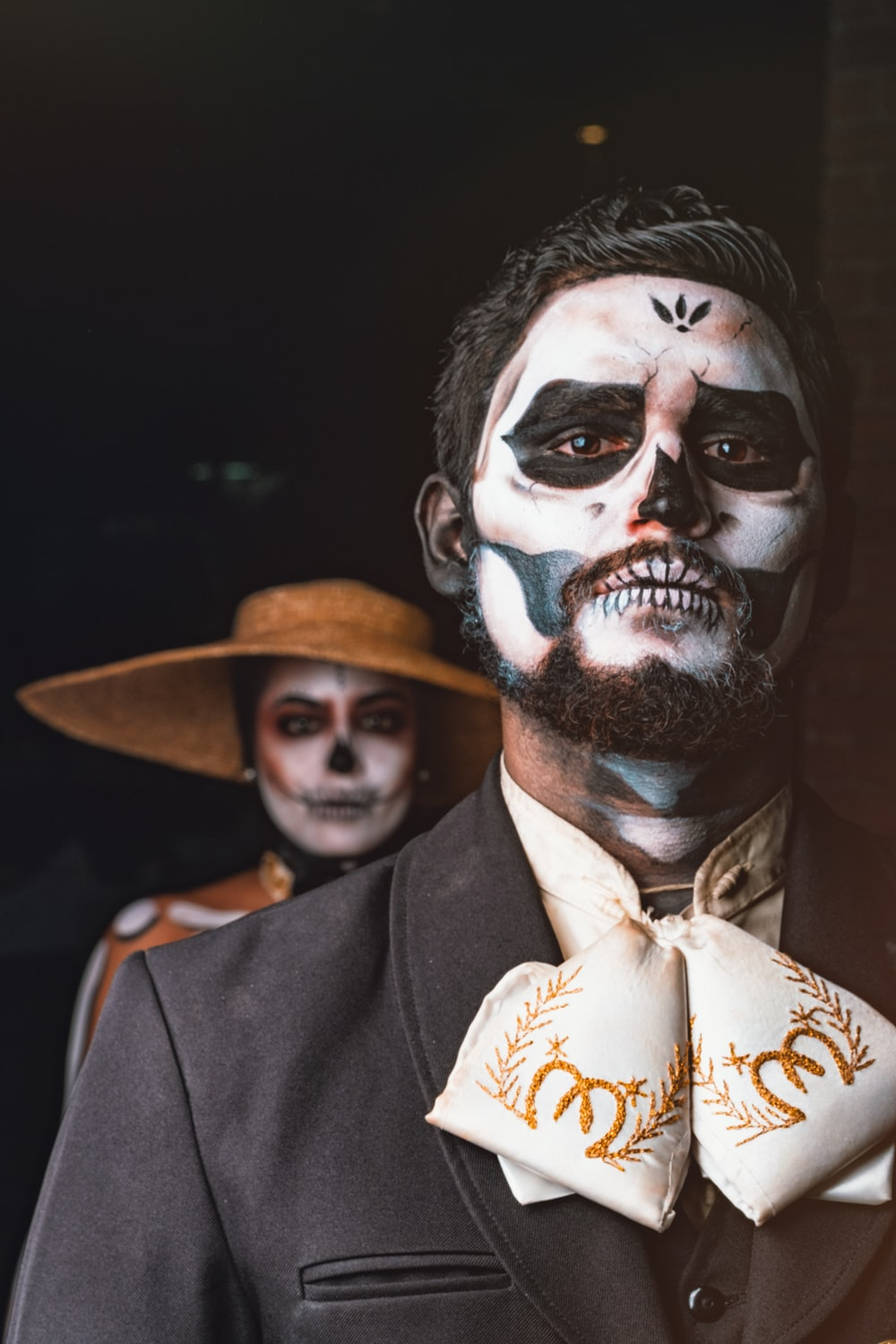 man in black suit with white and black face paint