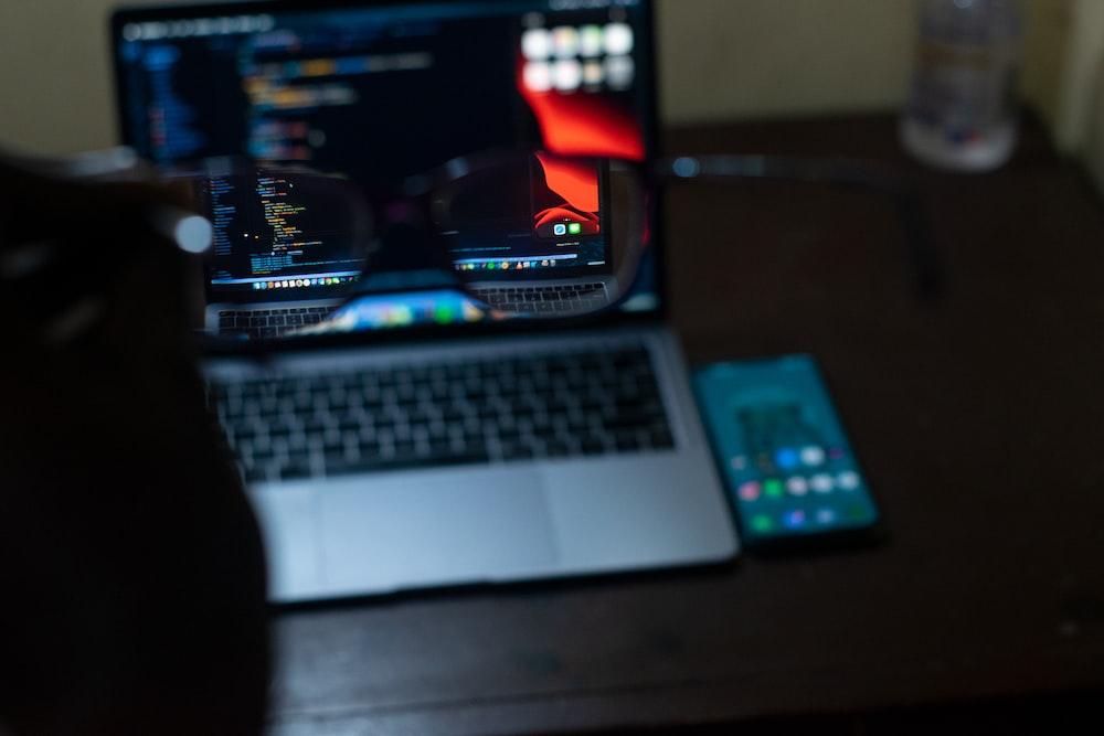 macbook pro beside black remote control