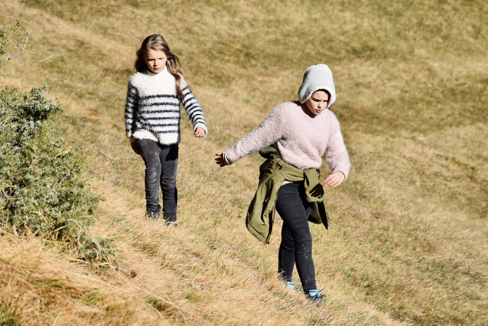 woman in pink sweater carrying child in black and white striped long sleeve shirt