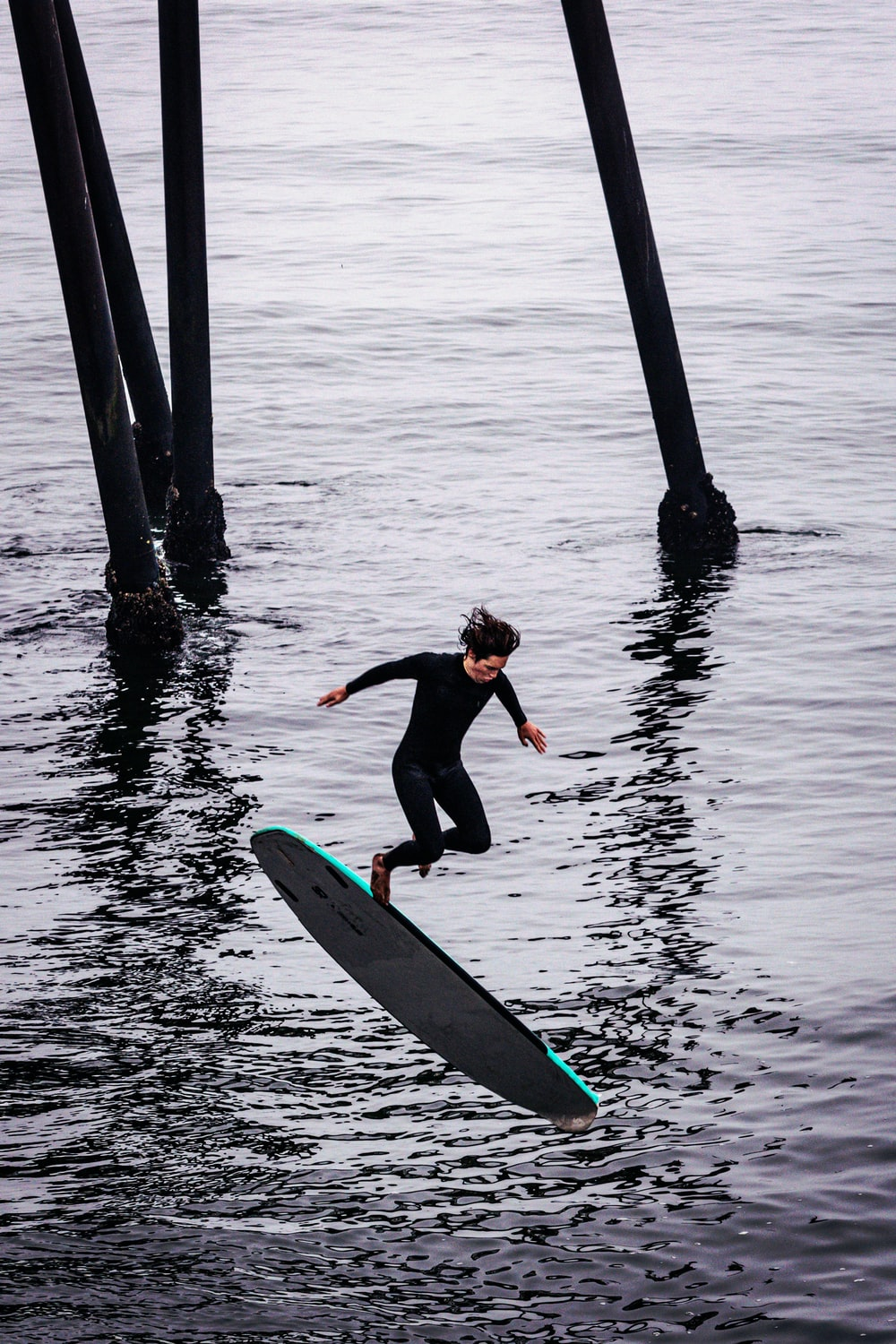 woman in black wetsuit riding on surfboard on body of water during daytime