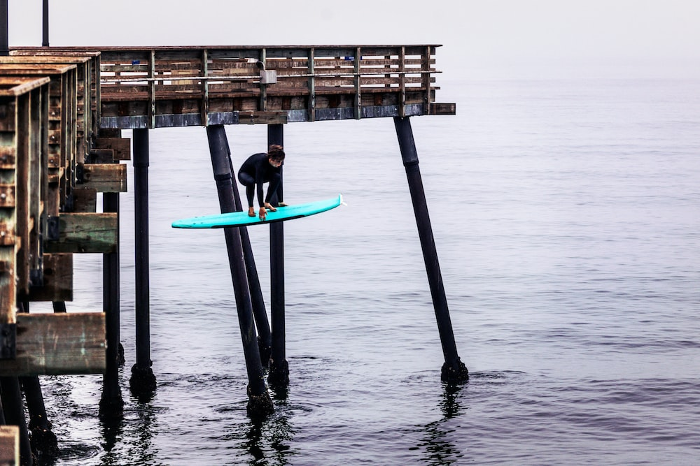 person in black wet suit holding blue surfboard on sea during daytime