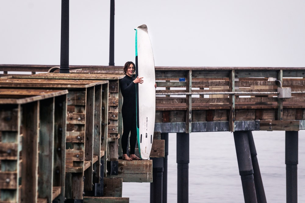 woman in white and black long sleeve dress standing on wooden dock during daytime