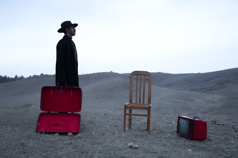 man in black jacket and black hat standing near red chair