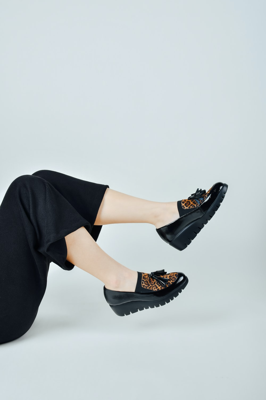 woman in black pants wearing black leather peep toe heeled shoes
