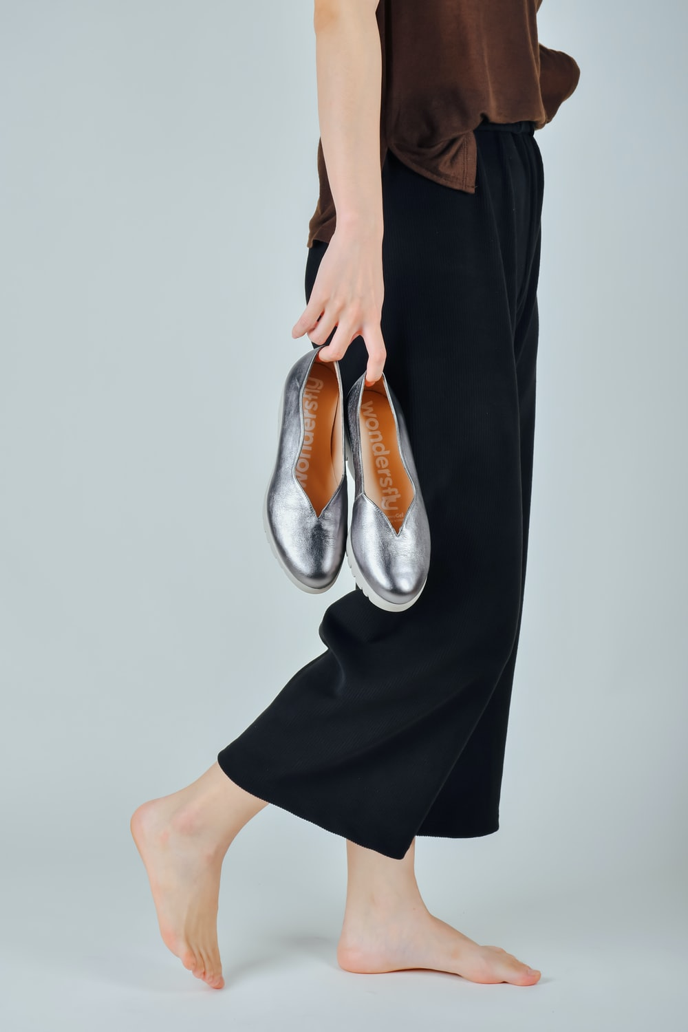 woman in black dress wearing brown leather flats