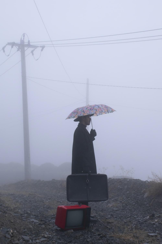person standing under umbrella during daytime