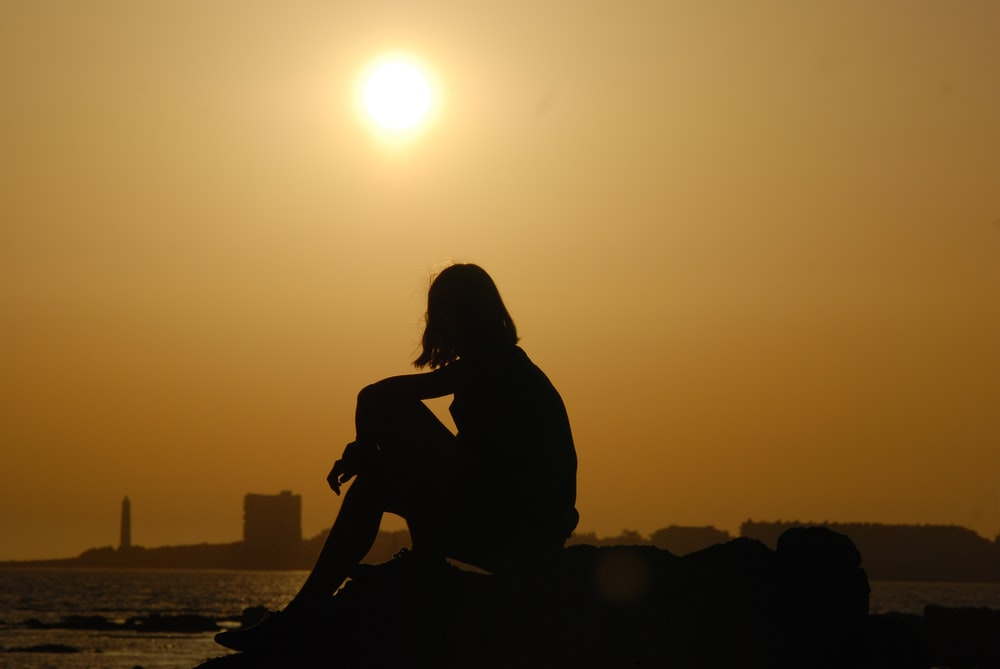 silhouette of woman sitting on rock during sunset