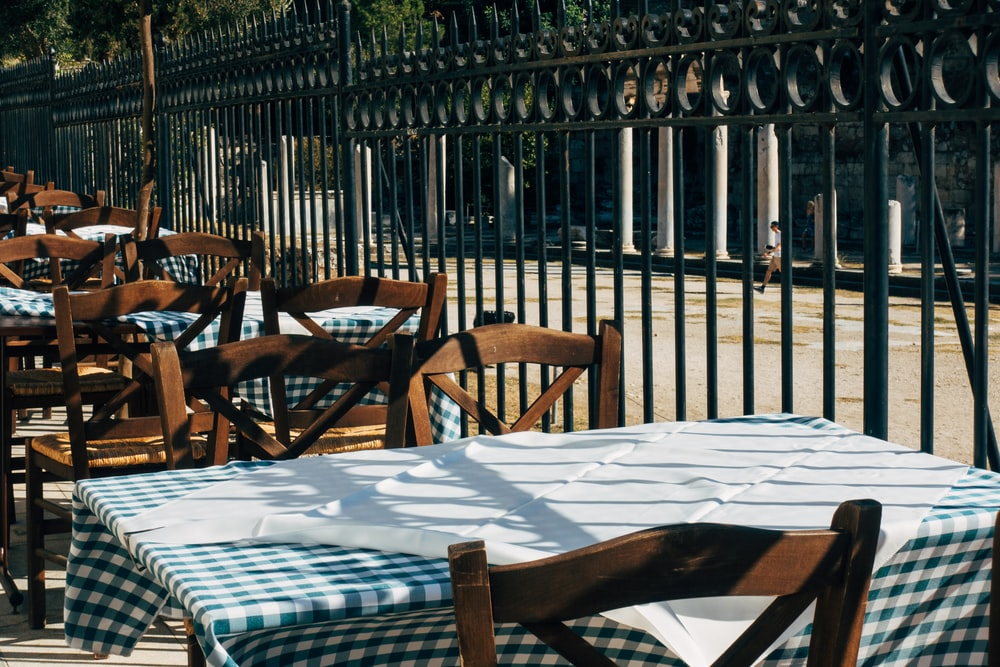 brown wooden chairs and table covered with white table cloth