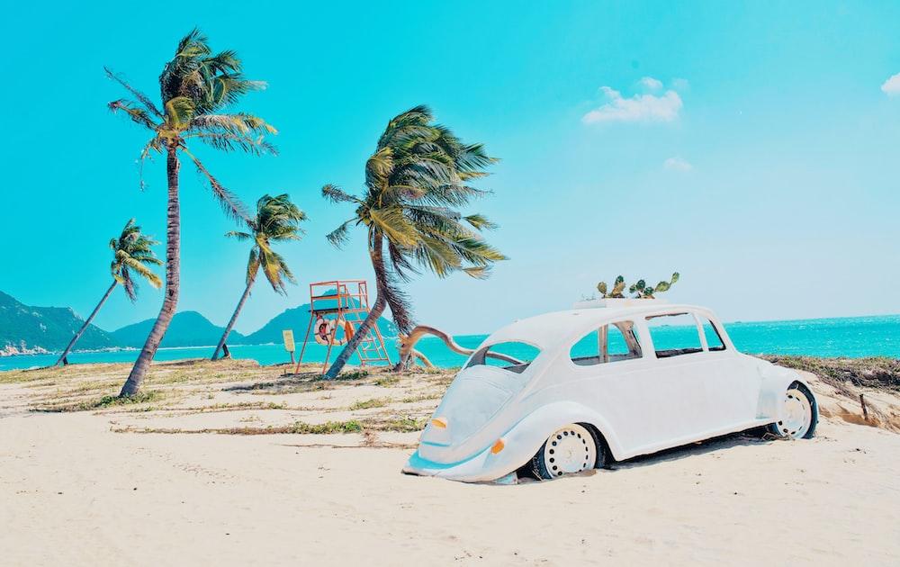 white volkswagen beetle on beach during daytime