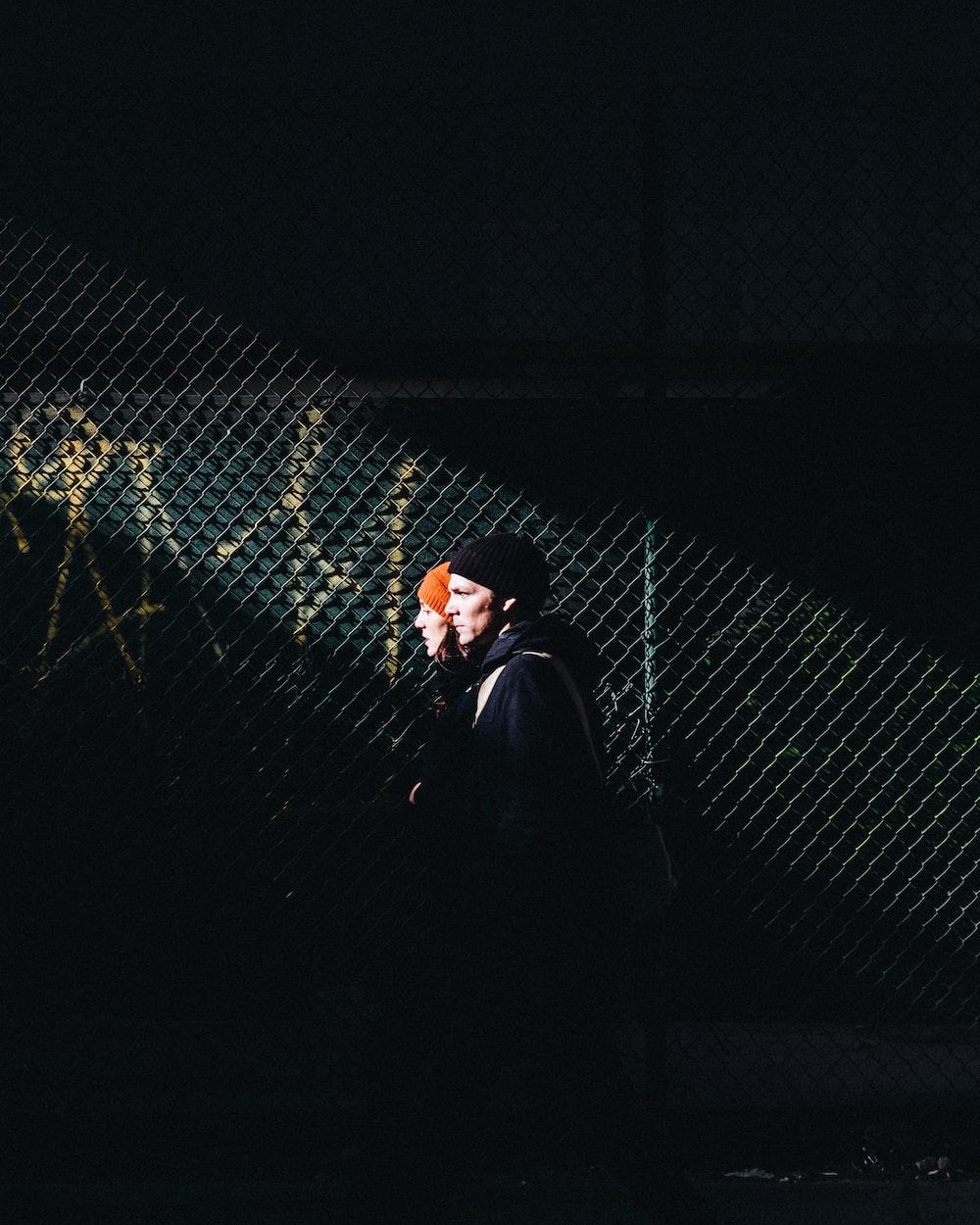 man in black leather jacket standing beside metal fence