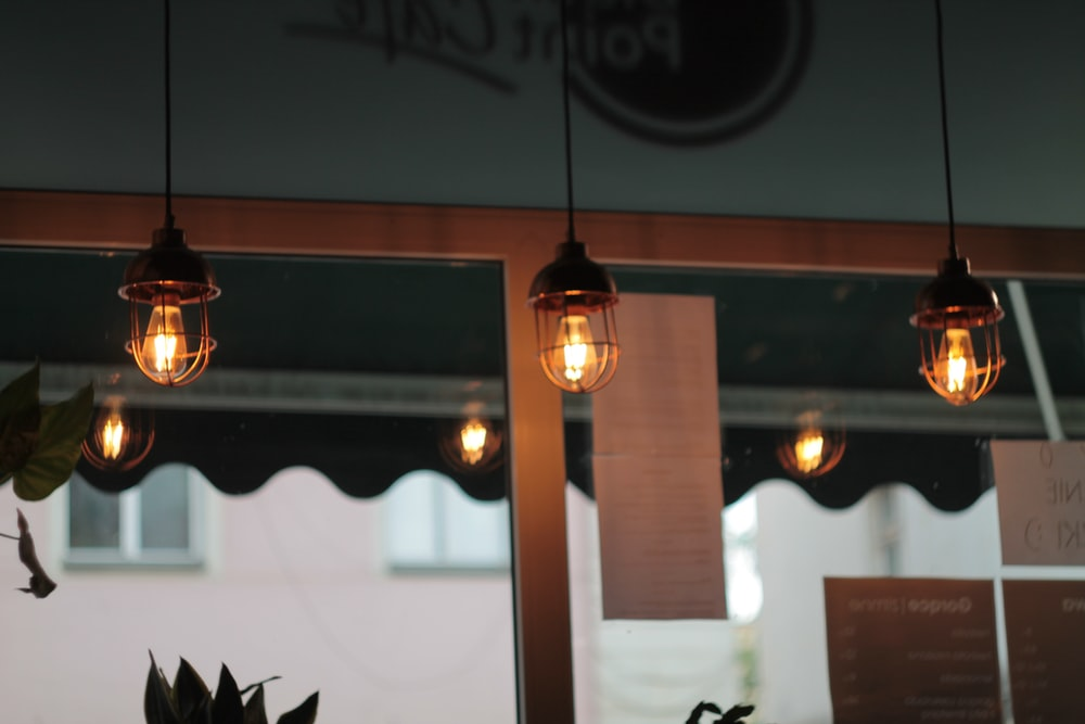 brown pendant lamp turned on during daytime