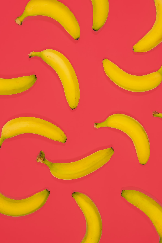 yellow banana fruits on pink surface