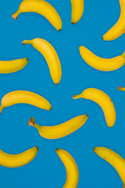 yellow banana fruits on blue surface