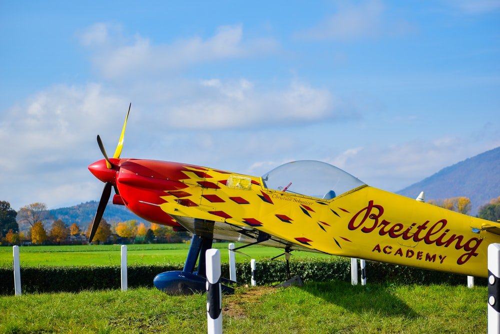blue and yellow jet plane on green grass field under white clouds and blue sky during