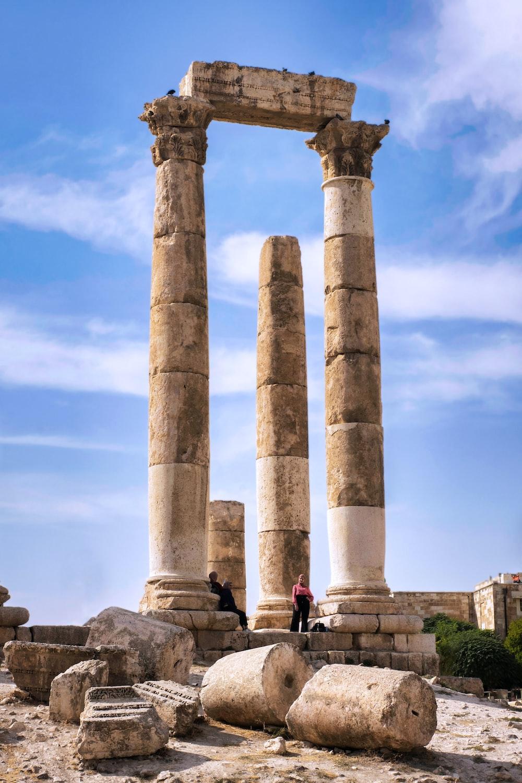 people walking on gray concrete pillar under blue sky during daytime