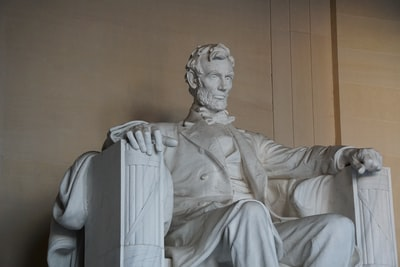 man in white robe statue lincoln memorial teams background