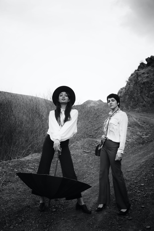2 women standing on grass field during daytime