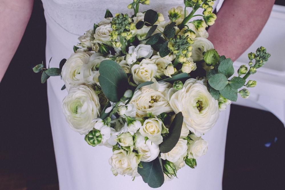 white roses bouquet on white textile