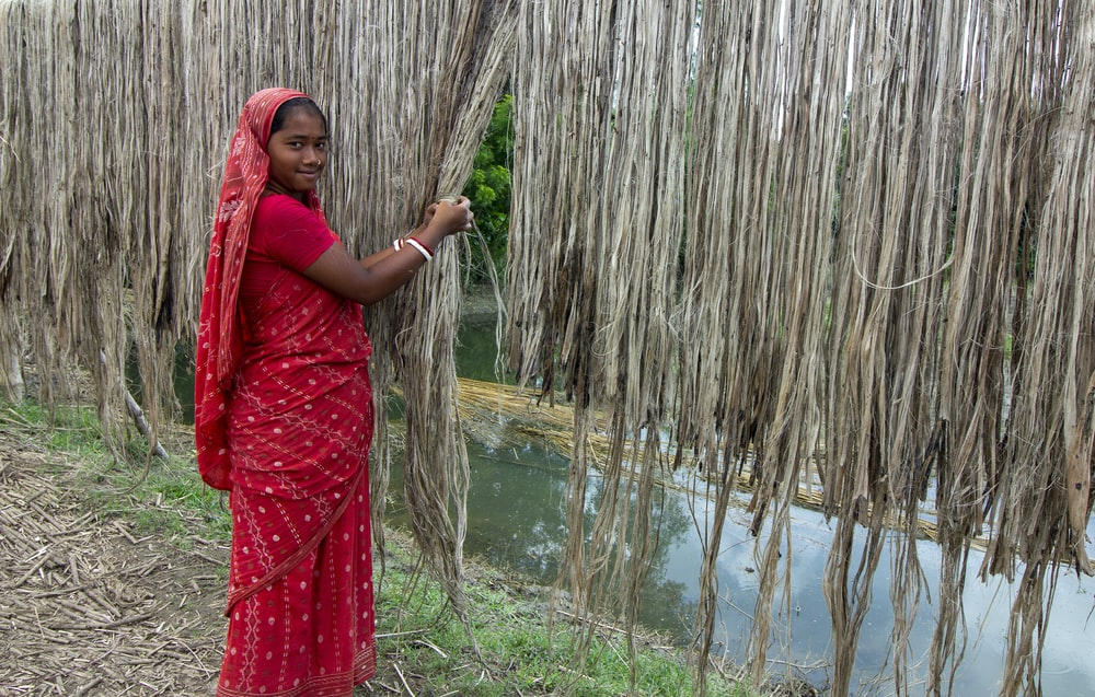 woman in red hijab standing near brown bamboo tree during daytime