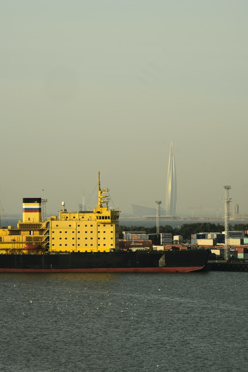 red and yellow cargo ship on sea during daytime
