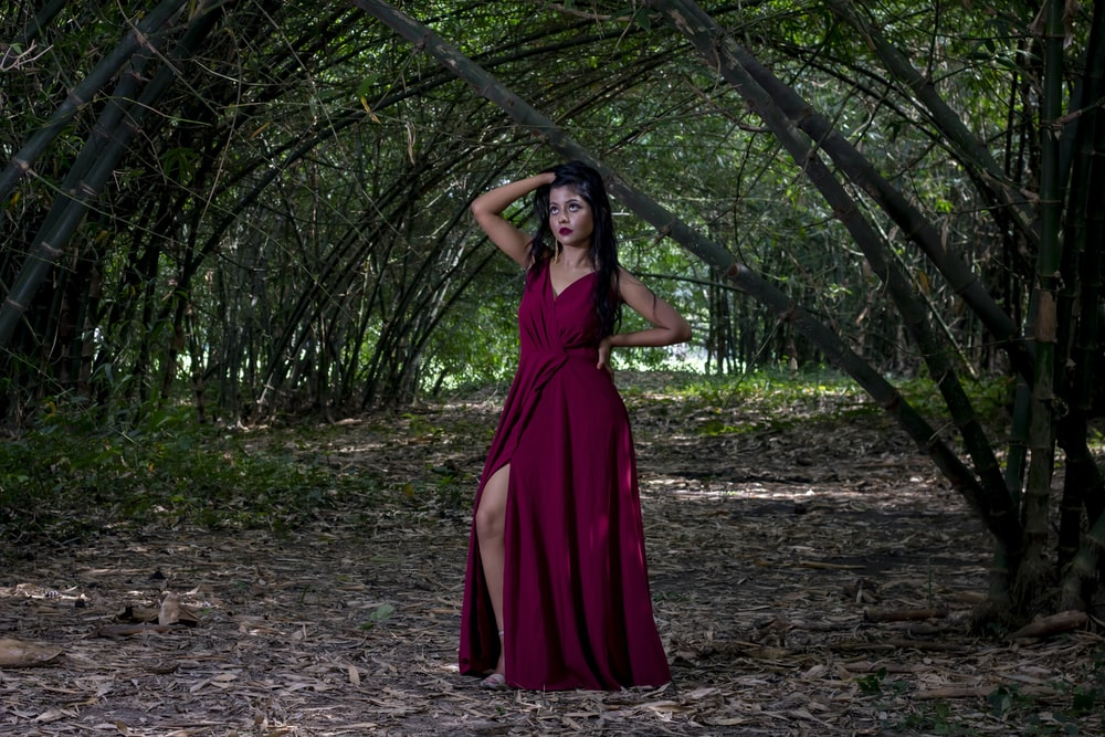woman in red sleeveless dress standing under the tree
