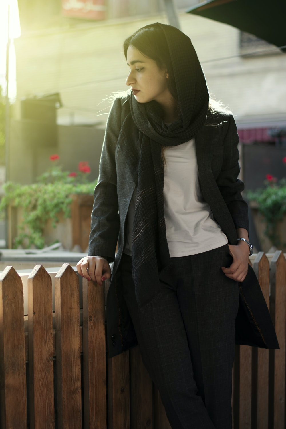 woman in black pants and gray scarf standing beside brown wooden fence