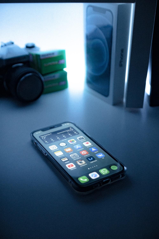 black iphone 5 beside black sony speaker