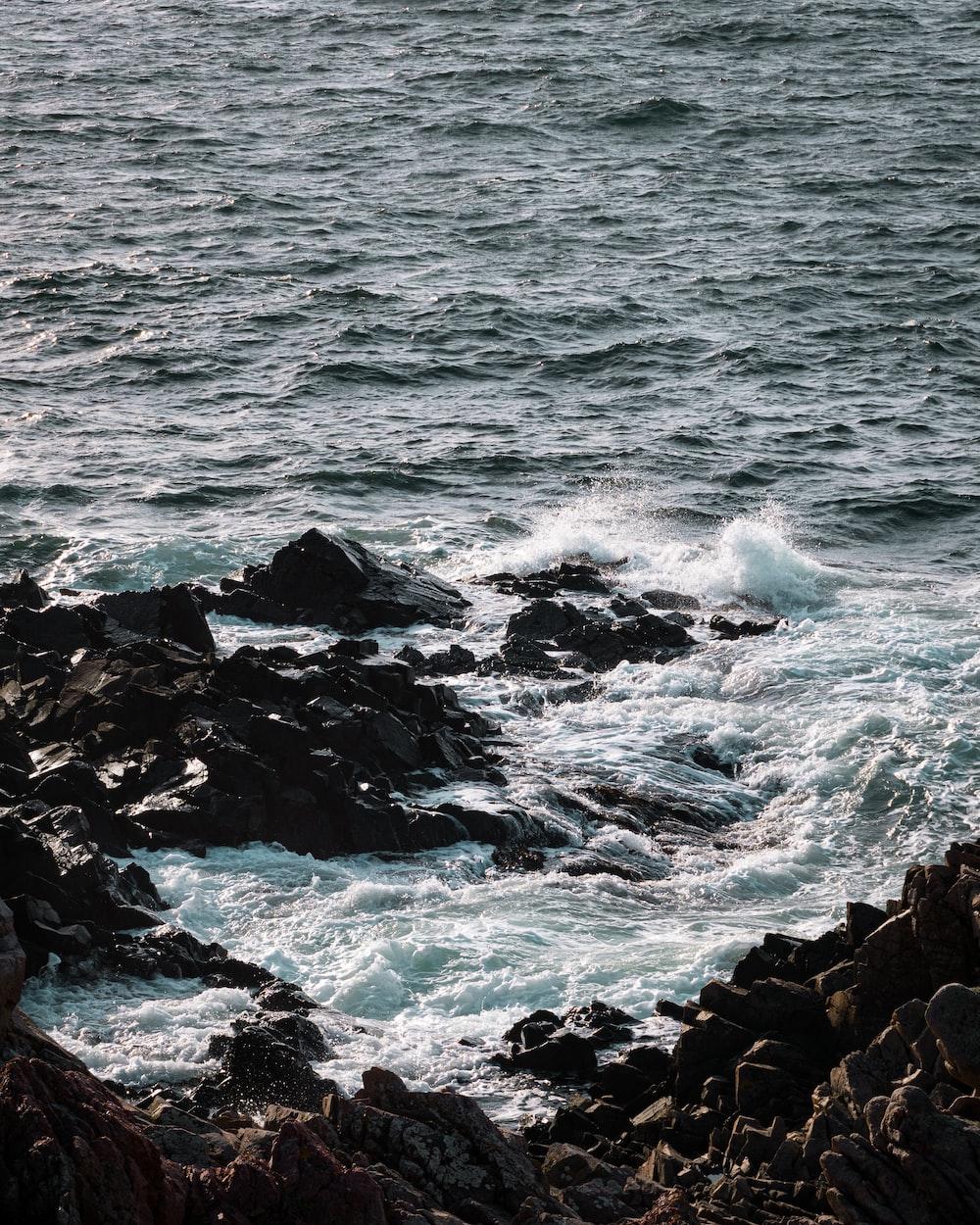 black rocky shore with ocean waves crashing on rocks during daytime