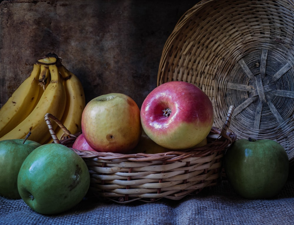 green apples and apples on brown woven basket