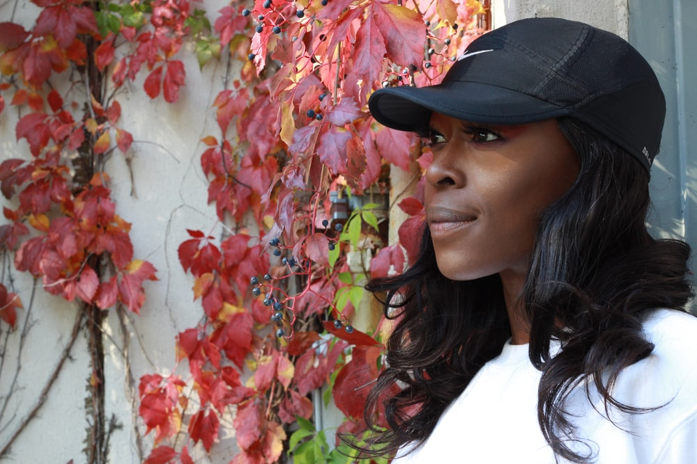 woman in white shirt wearing black cap standing beside red and yellow leaves