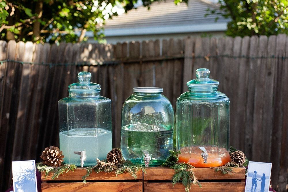 four clear glass jars on brown wooden table