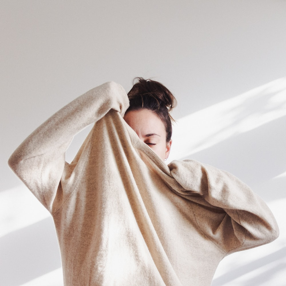woman in white long sleeve shirt covering her face with brown scarf