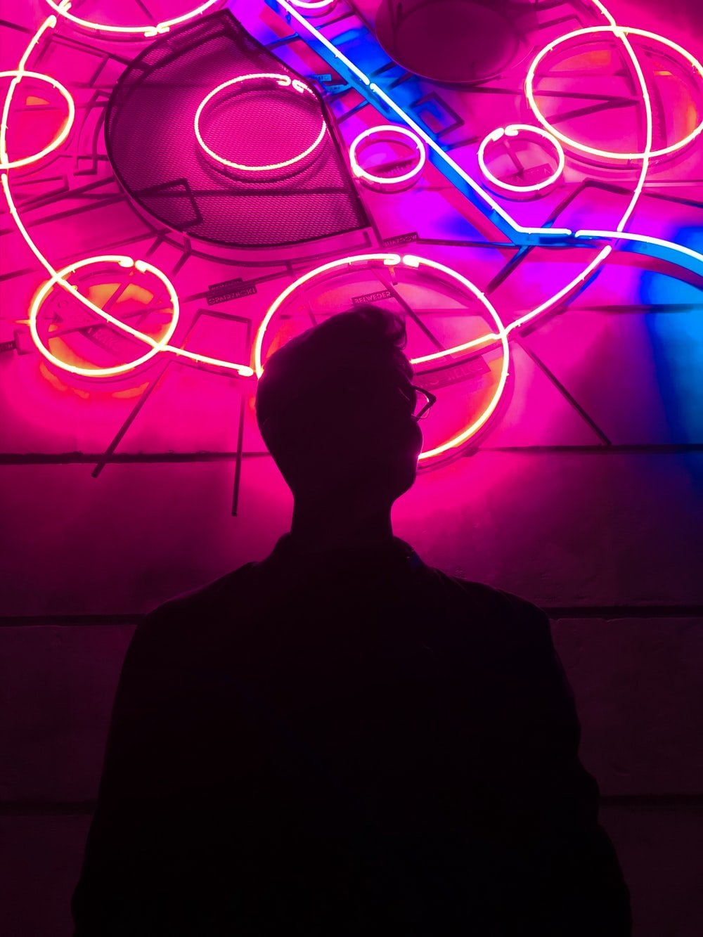 silhouette of man standing in front of neon light