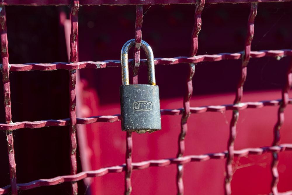 brass padlock on red metal fence