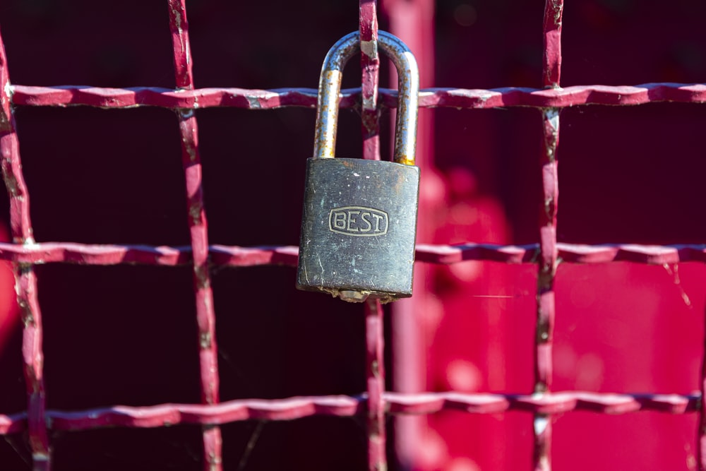 brass padlock on red metal fence