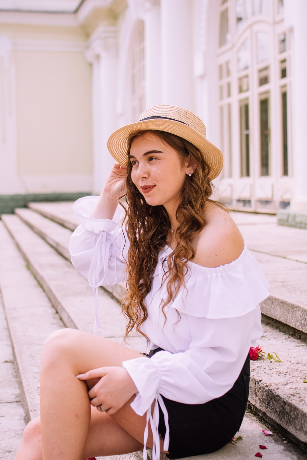 woman in white off shoulder dress wearing brown hat sitting on concrete floor during daytime