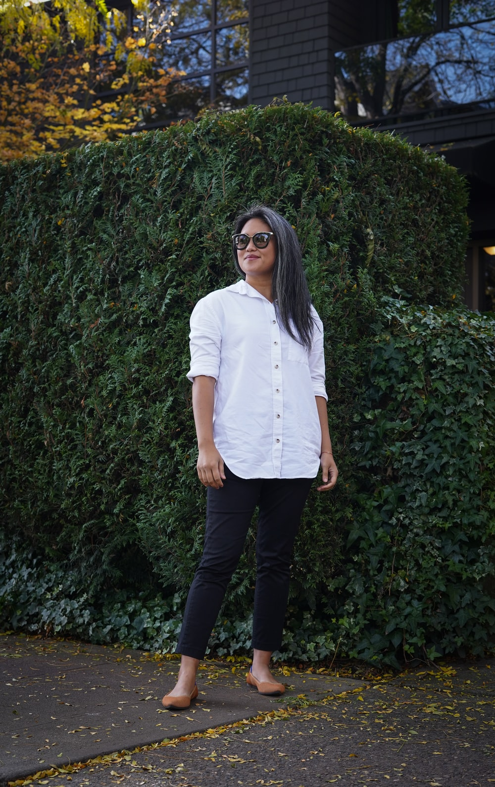 woman in white button up shirt and black pants standing near green plants during daytime