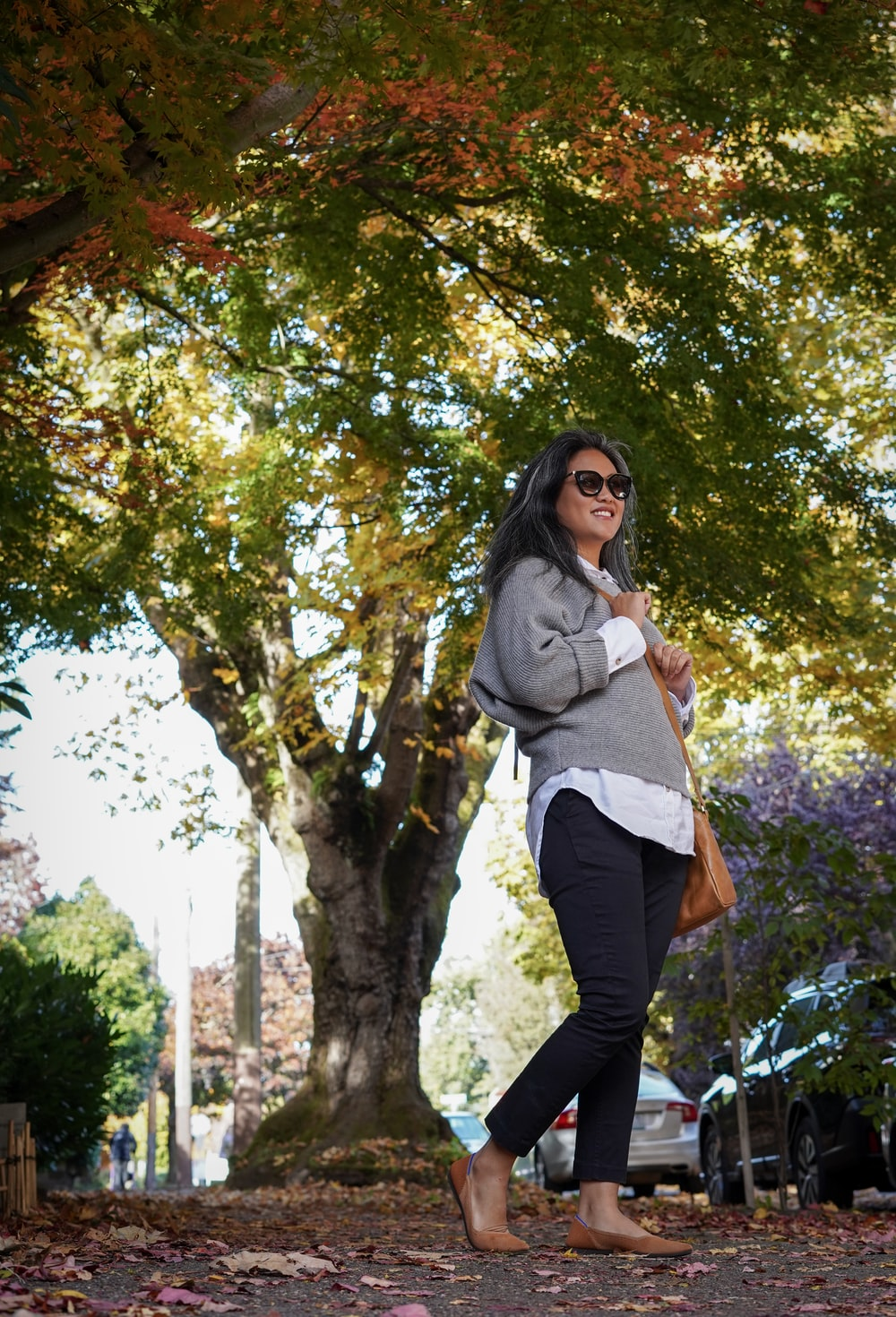 woman in gray long sleeve shirt and black pants standing under green tree during daytime