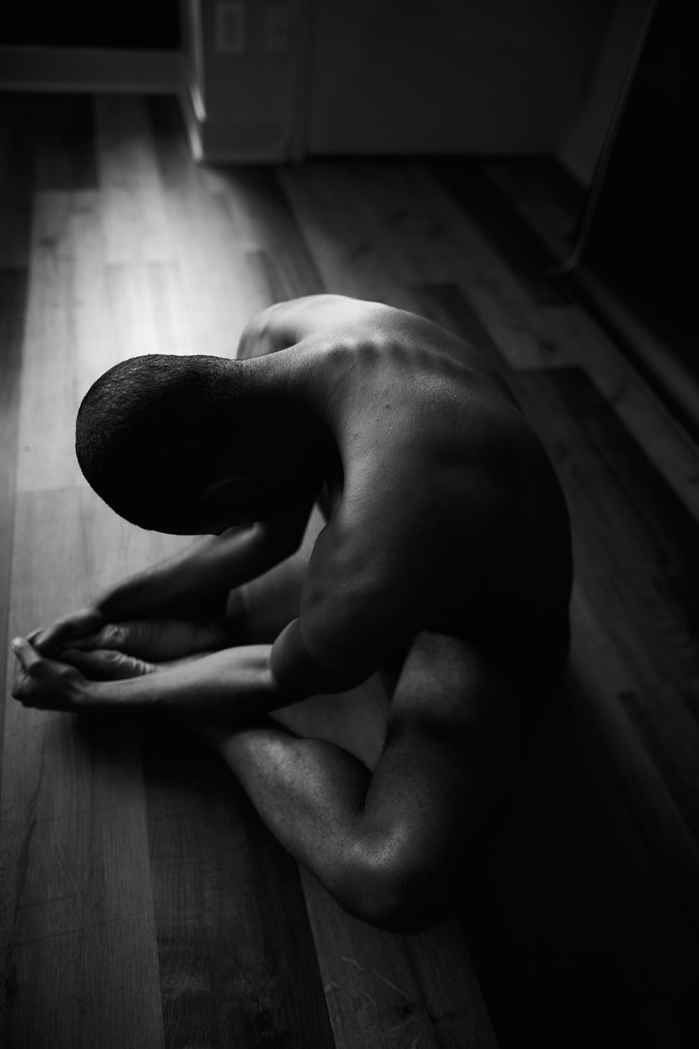 grayscale photo of man kneeling on floor
