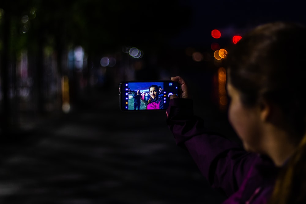 person holding smartphone taking photo of city during night time