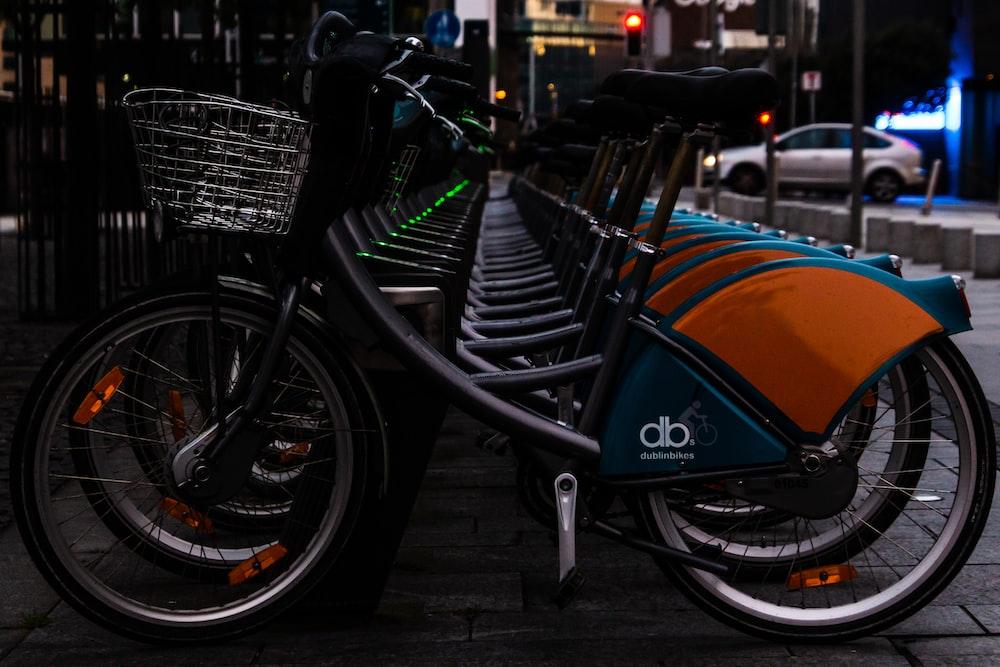 black and blue bicycle on black steel bicycle rack