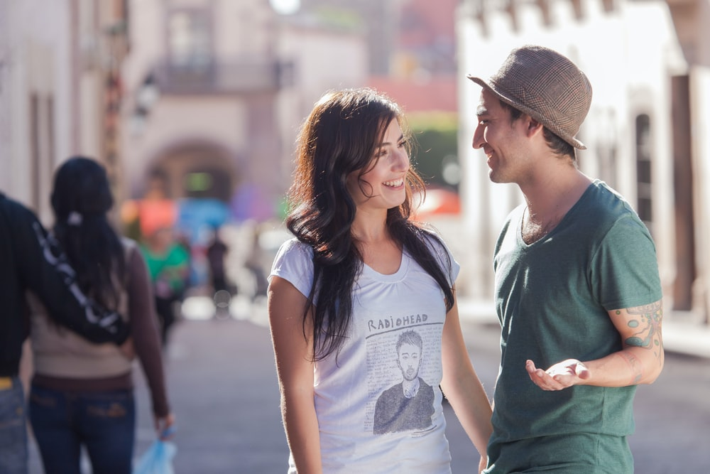 woman in gray crew neck t-shirt and gray fedora hat standing beside woman in gray