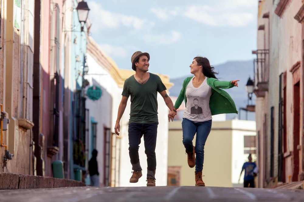 man in green t-shirt and woman in white t-shirt walking on street during daytime